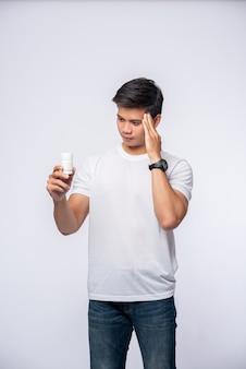 Ein mann mit schmerzen in der hand hält eine medizinflasche und die andere hand aber auf dem kopf