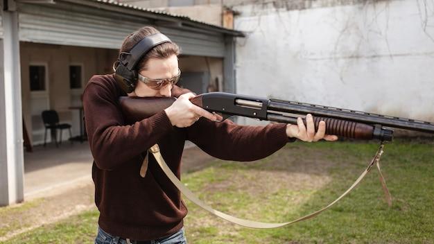 Ein mann mit schutzbrille und kopfhörern hält eine pumpgun