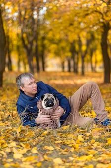 Ein mann mit seinem geliebten mops auf einem spaziergang im herbst im park.