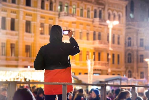 Ein mann mit smartphone nachts auf der stadtstraße