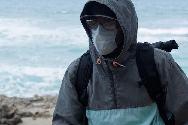Ein mann mit sonnenbrille trägt einen hoodie mit einer medizinischen maske im gesicht.