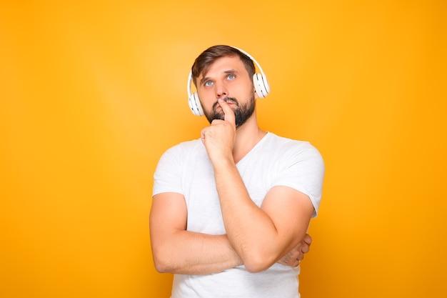 Ein mann mit weißen kopfhörern hört musik und grübelt, legt sich die hand vors gesicht.