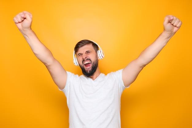 Ein mann mit weißen kopfhörern hört musik und singt laut und hebt die hände.