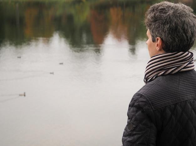 Ein mann mittleren alters fällt auf den hintergrund der natur. mann der rücken schaut in die ferne. der mann im schal.