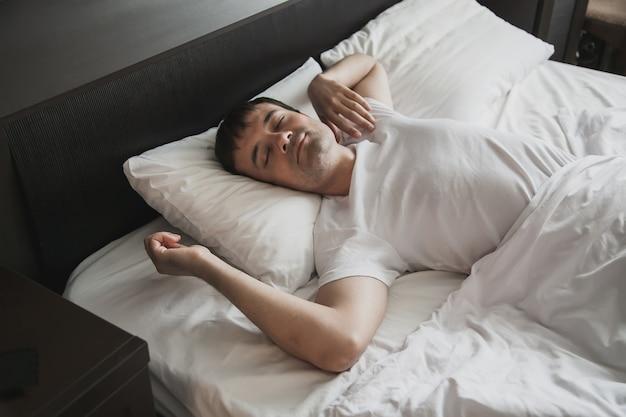 Ein mann mittleren alters im bett in seinem schlafzimmer wacht morgens mit einem lächeln auf dem gesicht auf. das konzept des gesunden schlafs.