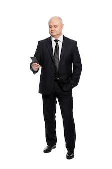 Ein mann mittleren alters in einem strengen schwarzen anzug schaut auf das telefon. vollständige höhe. auf weißer wand isoliert. vertikal.