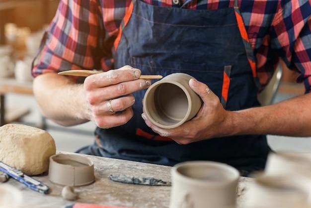 Ein mann mittleren alters in einer einheitlichen arbeit von holzstapel mit einer tonform tasse in einer großen kreativen keramikmanufaktur.