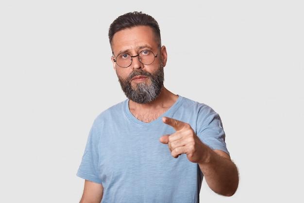 Ein mann mittleren alters in halber länge mit entblößtem gesicht, zeigefinger und grauem t-shirt und brille trägt einen selbstbewussten und ernsten gesichtsausdruck. ich habe dich ausgewählt.
