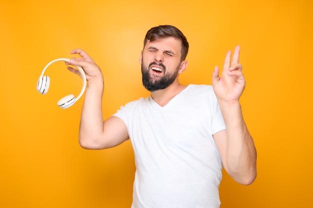 Ein mann - musikliebhaber in einem weißen t-shirt, hält weiße musikkopfhörer in den händen.