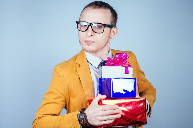 Ein mann-nerdy-freak mit brille und einem gelben stylischen anzug hält kisten mit geschenken in den händen. konzept der feier, großzügigkeit und shoppoholism