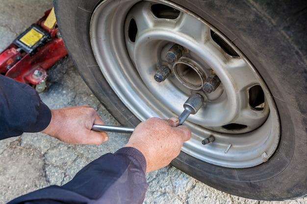 Ein mann nimmt ein abgenutztes rad aus seinem auto, um es durch ein neues zu ersetzen