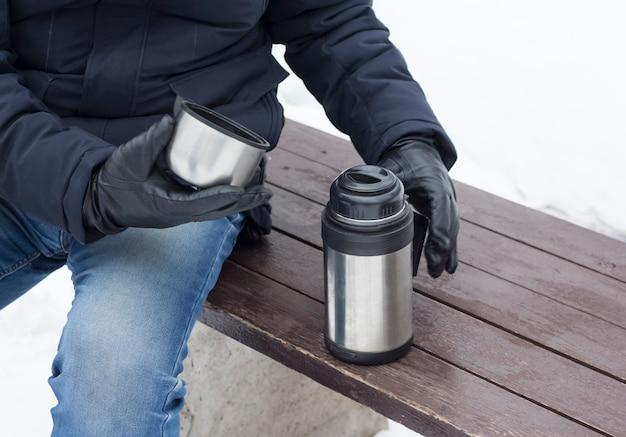 Ein mann öffnete im winter eine thermoskanne mit heißem kaffee auf einer parkbank, um zu trinken und sich aufzuwärmen.