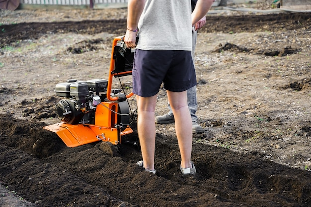 Ein mann pflügt den boden mit einem pinnenblock im garten. der landwirt pflügt das land mit einem grubber, der den boden für die aussaat vorbereitet.