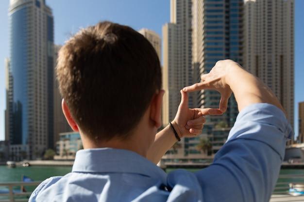 Ein mann plant einen zukünftigen fotorahmen, macht einen rahmen aus seinen fingern.