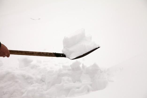 Ein mann putzt den schnee mit einer schaufel.