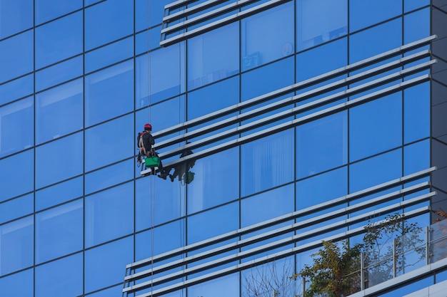 Ein mann putzt fenster in einem hochhaus. industriekletterer, der an der wäscheleine hängt und fenster wäscht, modernes gebäude der glasfassade