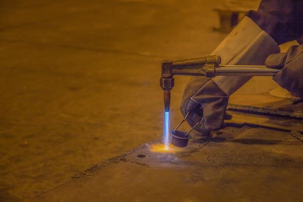 Ein mann qualifizierte fabrik schweißer arbeiten, schneiden, schleifen, bohren