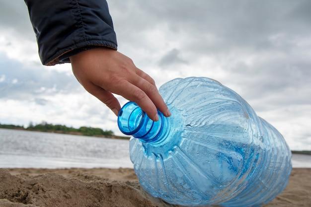 Ein mann räumt müll und plastikflaschen am schmutzigen strand auf, indem er sie einsammelt. umweltverschmutzung