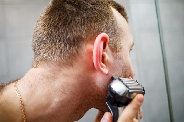Ein mann rasiert sich mit einem elektrorasierer vor einem spiegel das gesicht. hautreizung. badeverfahren