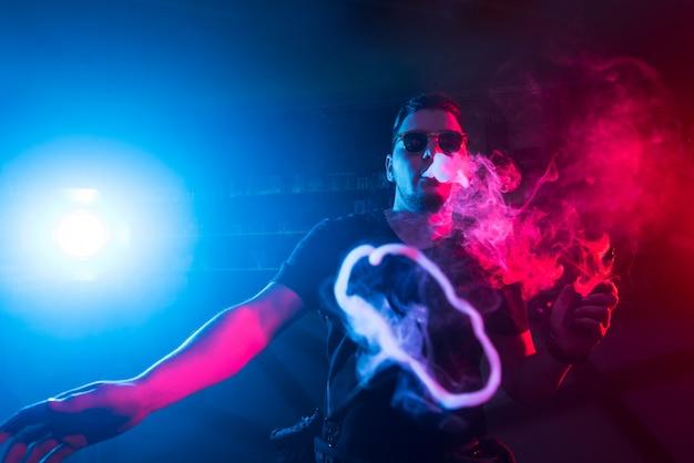 Ein mann raucht eine zigarette in einem nachtclub.