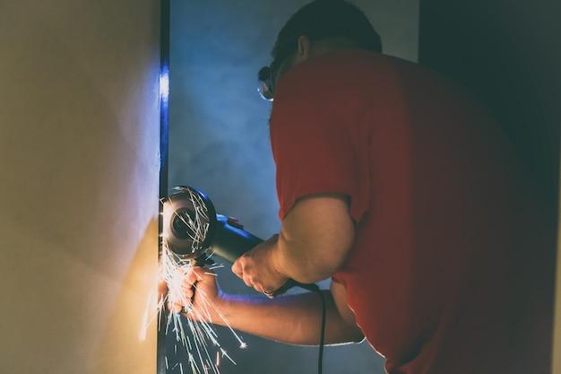 Ein mann repariert eine metalltür im keller seines hauses mit einer handschleifmaschine.