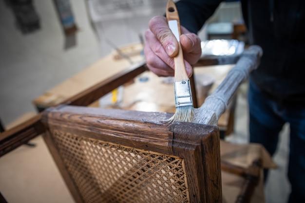 Ein mann restauriert eine kette, indem er sie mit einem gips bemalt