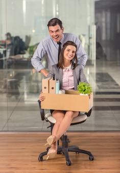 Ein mann rollt ein arbeitermädchen auf einem stuhl.