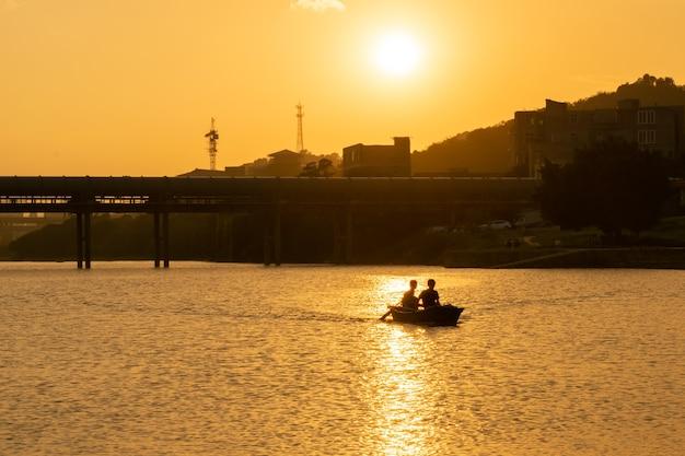 Ein mann ruderte auf einem see, der vom sonnenuntergang mit gold befleckt war