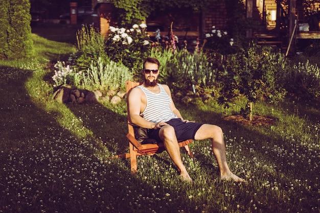 Ein mann ruht sich in einem landhaus aus. ein bärtiger mann genießt den sonnenuntergang auf einem grünen rasen.