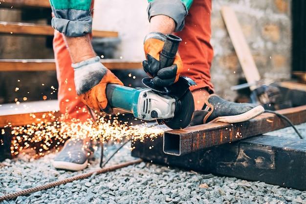 Ein mann sägt metall mit einem winkelschleifer. funken, nahaufnahme