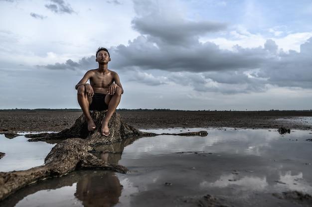 Ein mann saß mit gebeugten knien da und schaute zum himmel am fuße des baumes, umgeben von wasser.