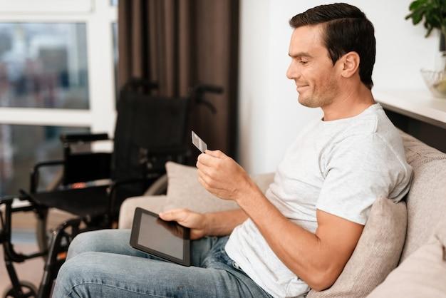 Ein mann schaut auf eine kreditkarte und gibt daten in das tablet ein.