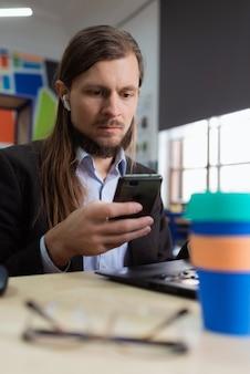 Ein mann schaut im büro mit ernstem gesicht auf sein handy phone