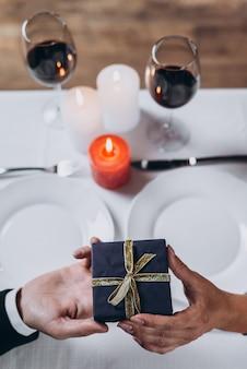 Ein mann schenkt einer frau beim abendessen ein geschenk