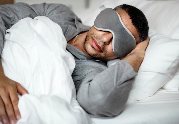 Ein mann schläft auf einem bett