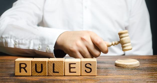 Ein mann schlägt einen hammer und veröffentlicht neue regeln und gesetze. festlegen klarer regeln und einschränkungen.