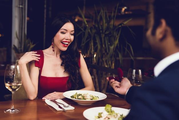 Ein mann schlägt einer frau vor und gibt ihr einen ring.