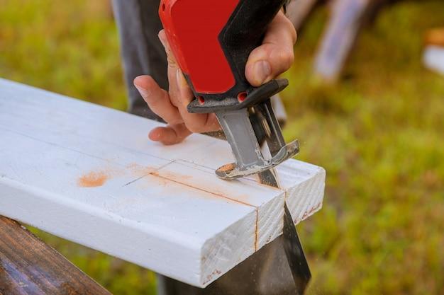Ein mann schneidet ein brett des holzes mit einem zackigen detail eines hölzernen brettes des ausschnitts mit sägemehl.