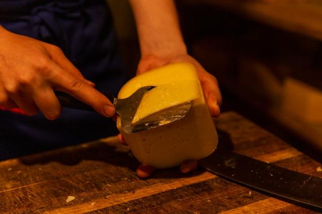 Ein mann schneidet käse in der produktion. landwirtschaftliche produktion von milchprodukten. nahansicht.