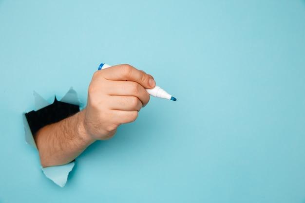 Ein mann schreibt einen marker auf eine zerbrochene blaue papierwand