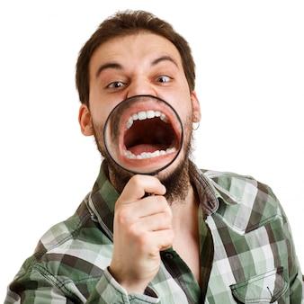 Ein mann schreit, sieht krumme zähne durch eine lupe.