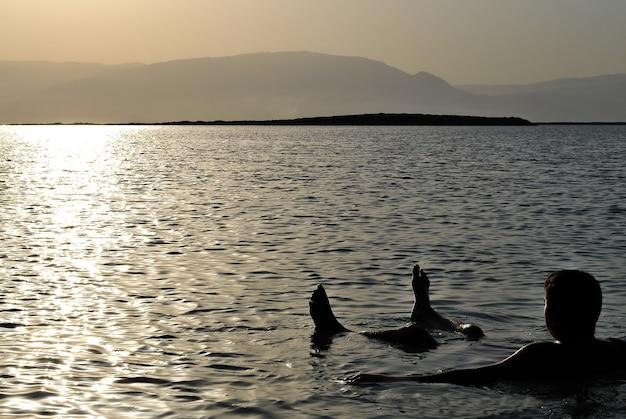 Ein mann schwimmt auf dem rücken im meer gegen die untergehende sonne. im hintergrund berge