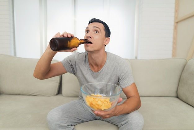 Ein mann sieht begeistert fern und trinkt bier