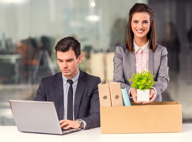 Ein mann sitzt am computer, während das mädchen dinge sammelt.