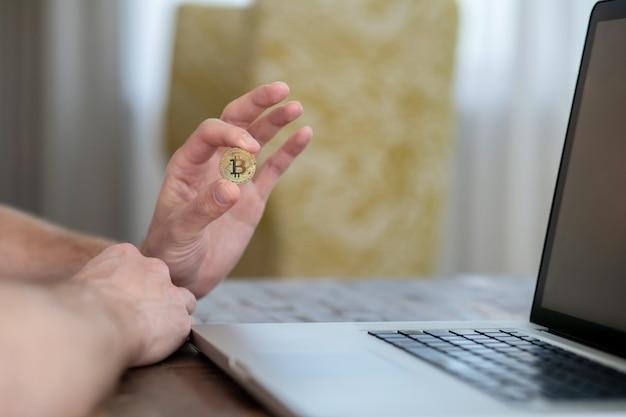 Ein mann sitzt am laptop und hält einen bitcoin
