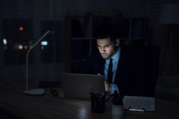 Ein mann sitzt an einem laptop in einem dunklen büro.