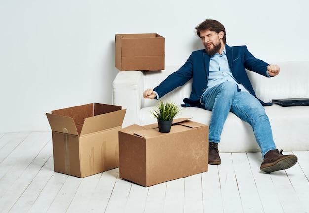 Ein mann sitzt auf der couch neben kisten und packt einen neuen umzugsort aus. hochwertiges foto