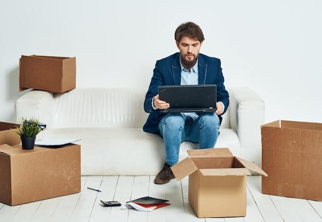Ein mann sitzt auf der couch vor einem laptop, der kisten mit dingen auspackt, die ein neues büro auspacken.