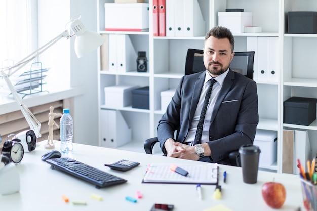 Ein mann sitzt auf einem stuhl im büro am tisch.