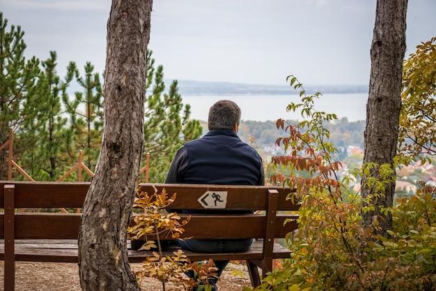 Ein mann sitzt auf einer bank am aussichtspunkt des lichtkreuzes (fenykereszt) auf der spitze des csandor-berges in vonyarcvashegy, ungarn
